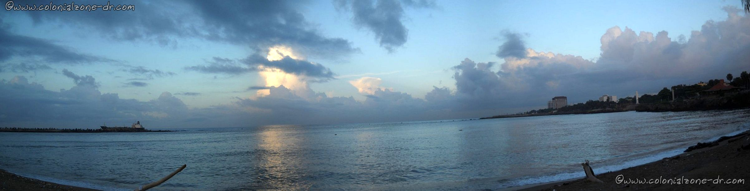 Panoramic view or the sun rising over the Caribbean Sea at the mouth of Rio Ozama in Ciudad Colonial, Santo Domingo, Dominican Republic. The reflection of the clouds on the water is breathtaking.