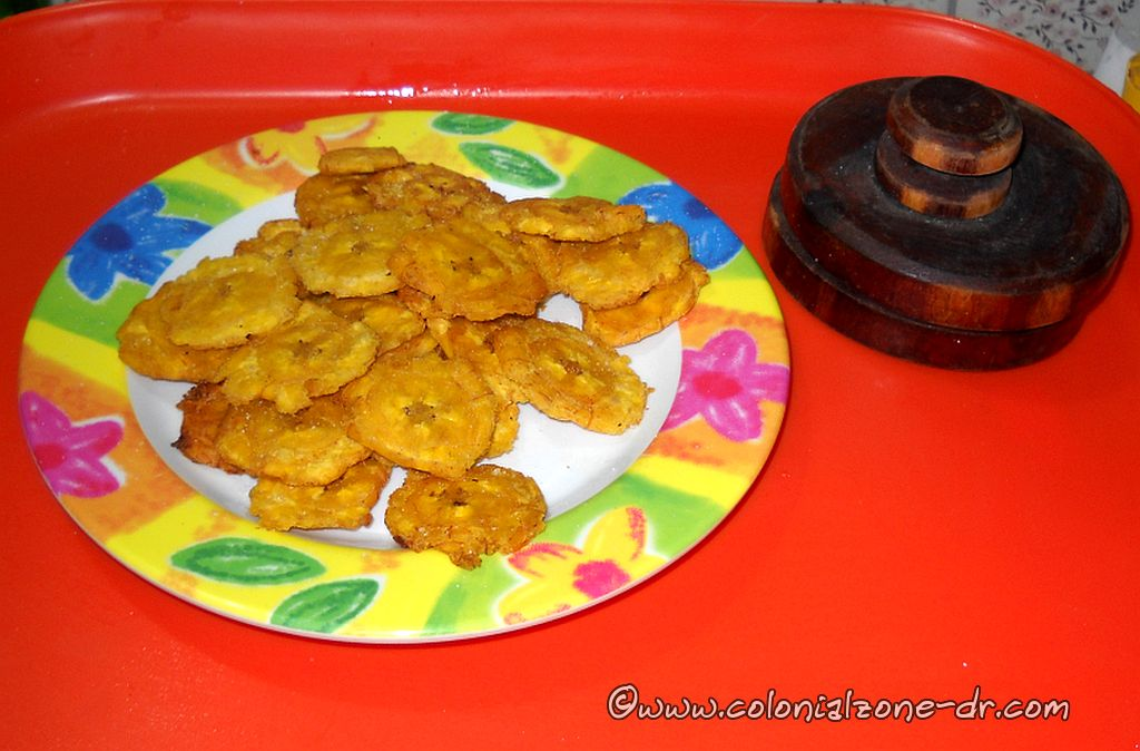 Tostones with a Tostonera beside the plate