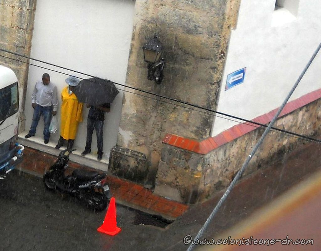 The police and others hiding from the rain in Cuidad Colonial, Santo Domingo. dominican republic