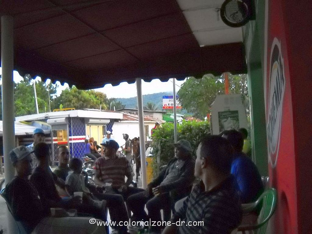 people gathering at a colmado in the coffee country