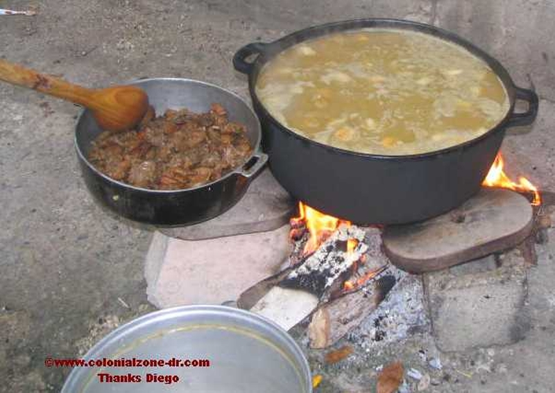Sancocho cooking on the fire with the meat ready to be added