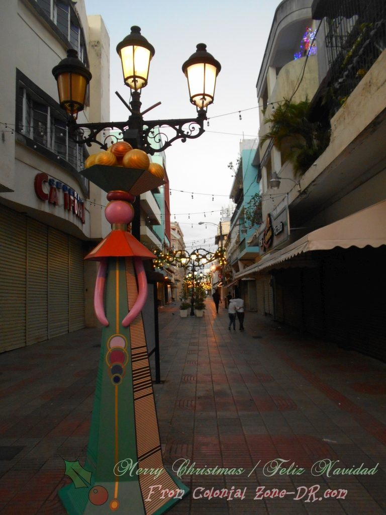 A life-sized Muñeca Sin Rostro / Faceless Doll on Calle el Conde with Christmas lights