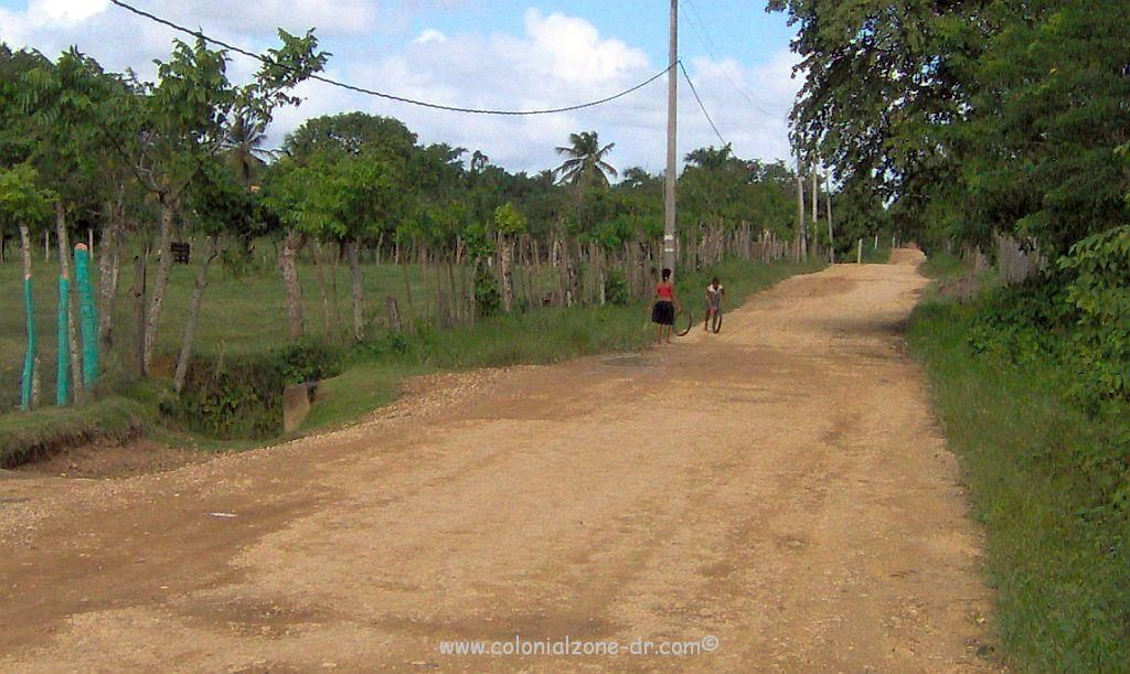 A dirt road in the campo. Little girls are rolling tired down the street.