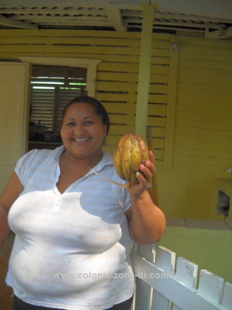 A woman proudly showing a Cacao/ Cocoa fruit in Dominican Republic.