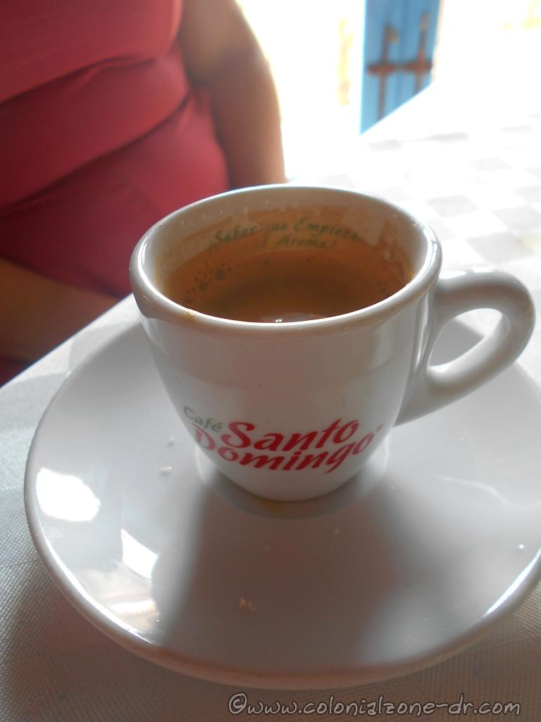 "A cup of hot Café Santo Domingo served in a restaurant. The cup interior says ""Sabor que empieza en el Aroma"" / Flavor that begins in the Aroma"