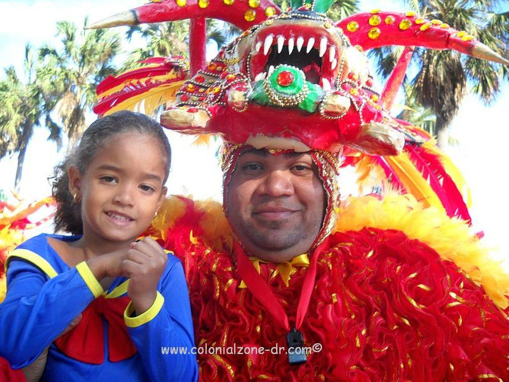 A happy little girl being held by a smiling Carnival Diablo.