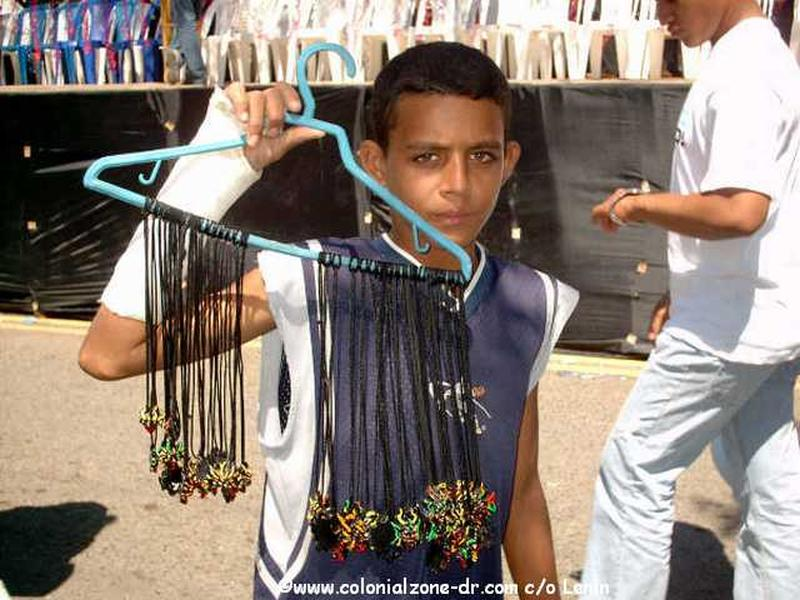 A young man selling little Diablo necklaces at carnaval.