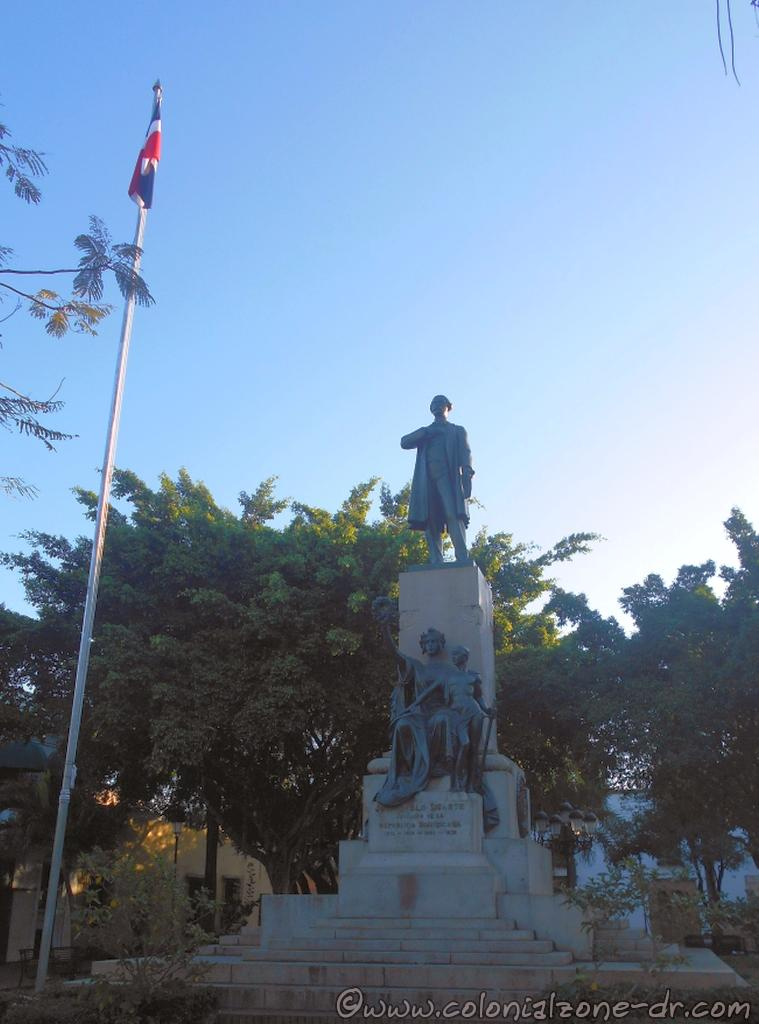 The bronze statue of Juan Pablo Duarte and the Dominican Flag in the center of Parque Duarte in the Colonial City of Santo Domingo.