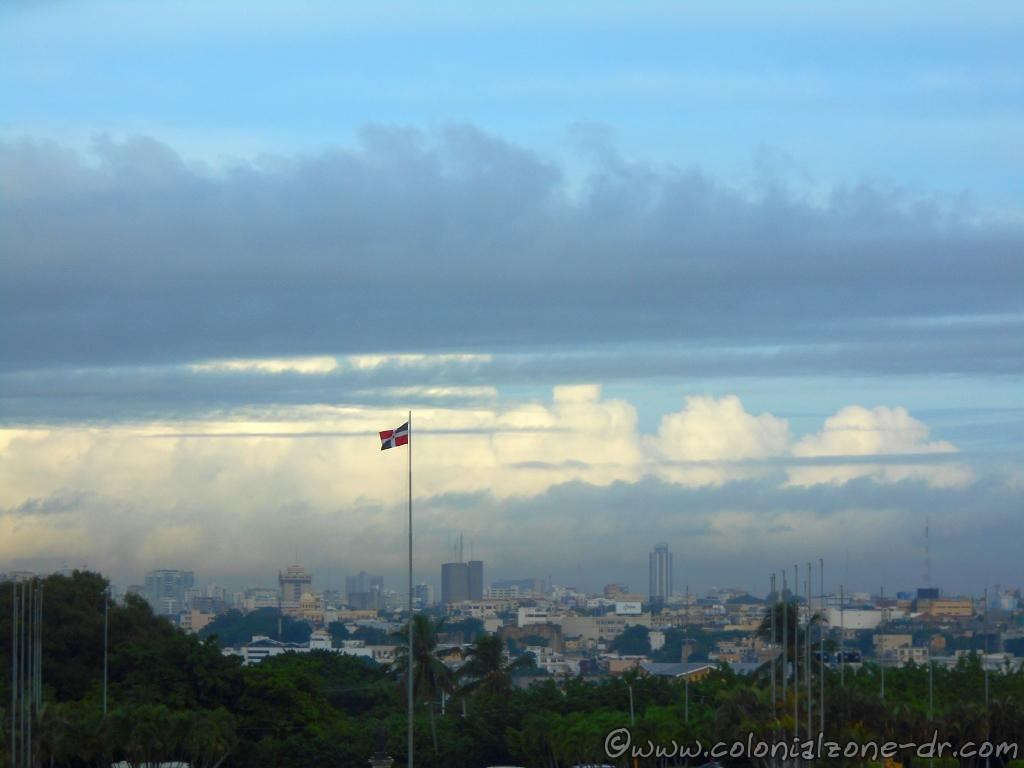 The Flag of Dominican Republic with the city of Santo Domingo in the distance as seen from the Faro a Colón