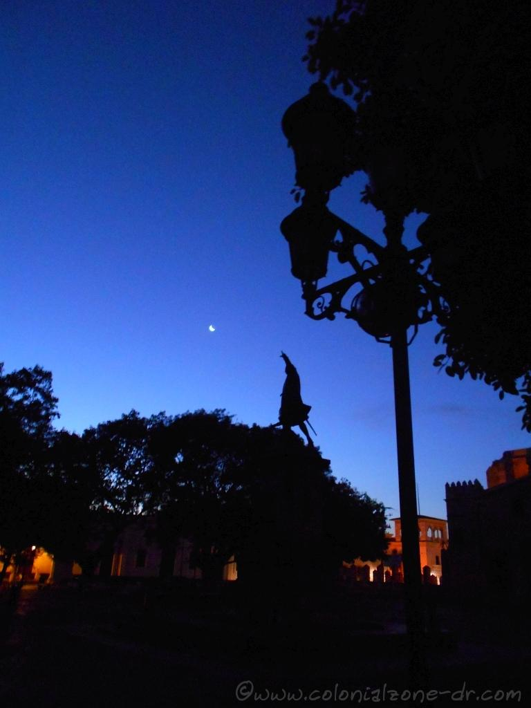 The shadow of the monument dedicated to Cristóbal Colón under a waning moon.